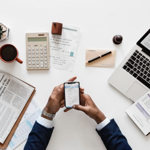 Bird's eye view of man holding phone at busy desk