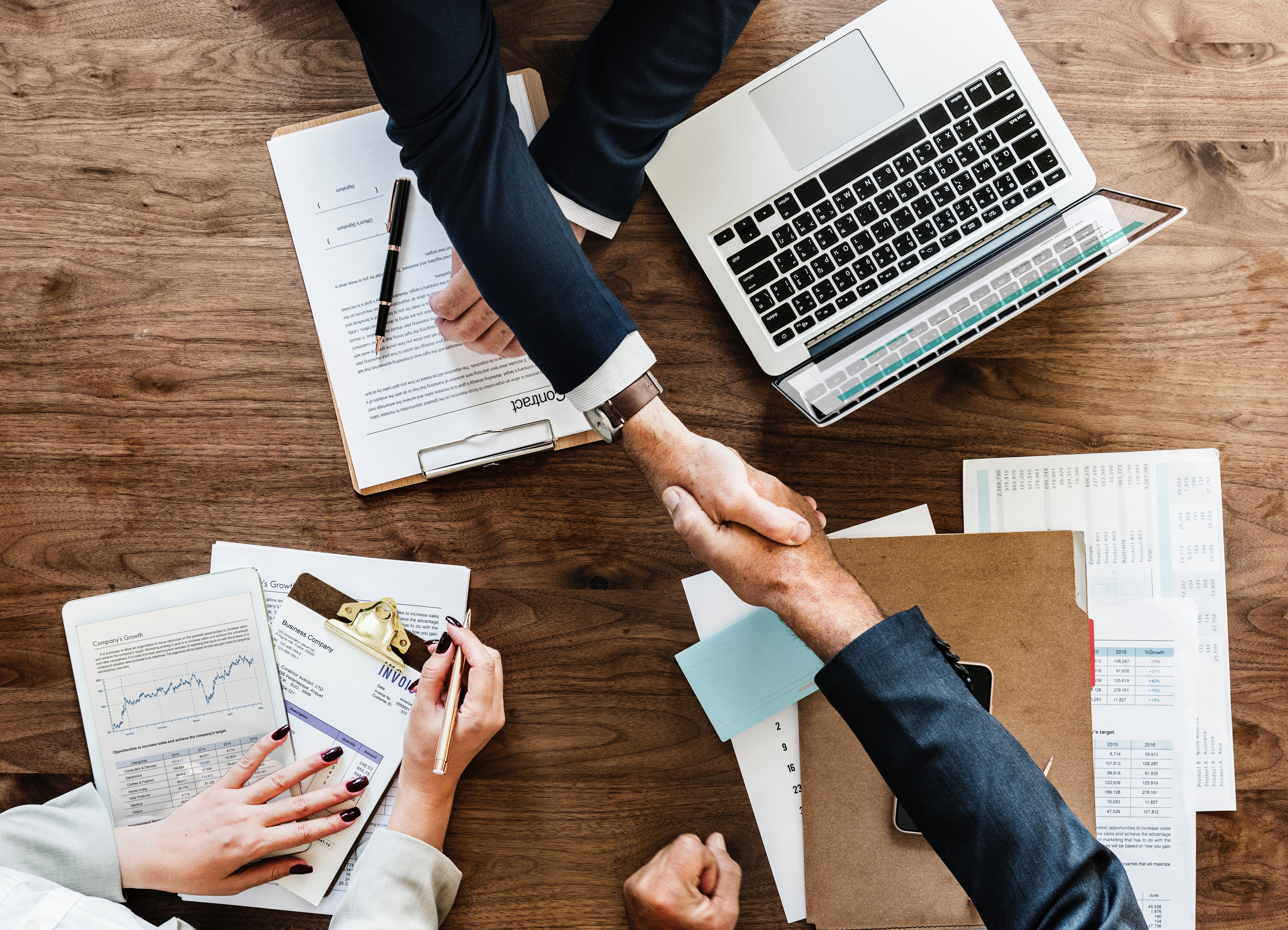Bird's eye view of two people shaking hands over desk