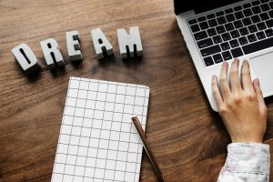 """Hand on laptop with notebook and """"Dream"""""""