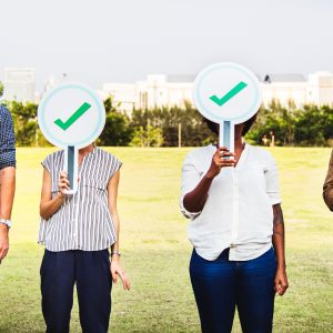 Four people holding check mark signs in front of their faces