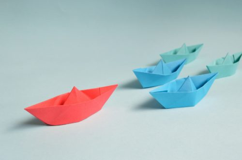 Origami blue boats following a red boat